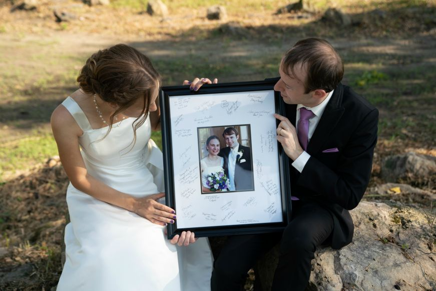 Stacy and Mike holding a large framed wedding photo