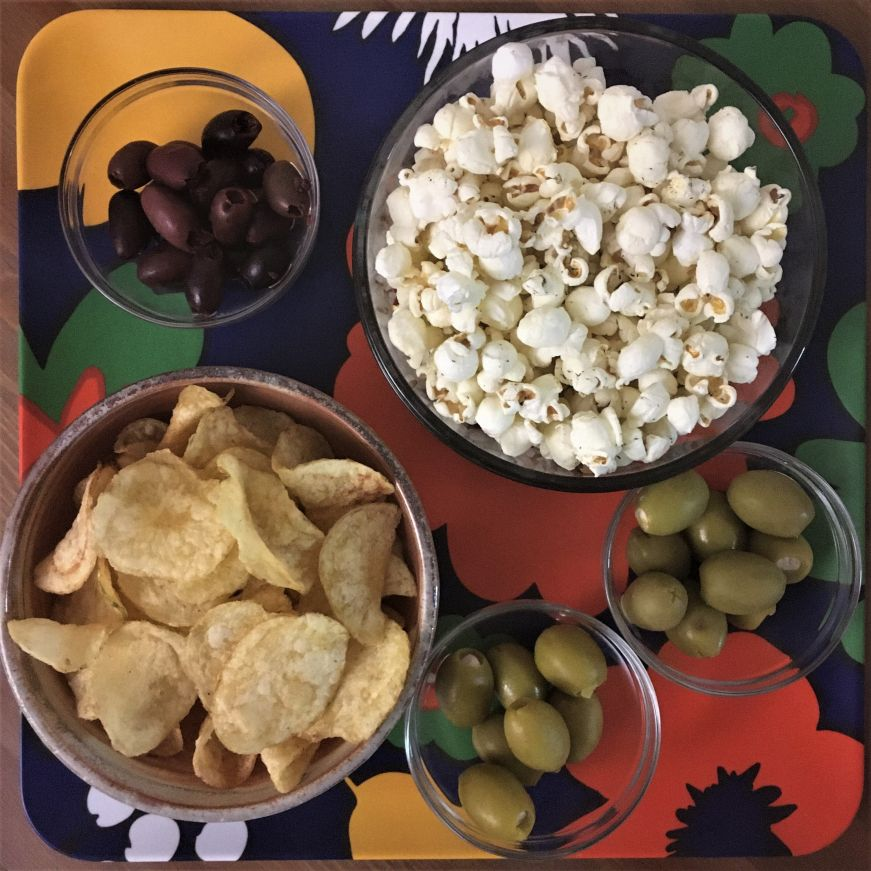 Tray with bowls of popcorn, chips, and olives