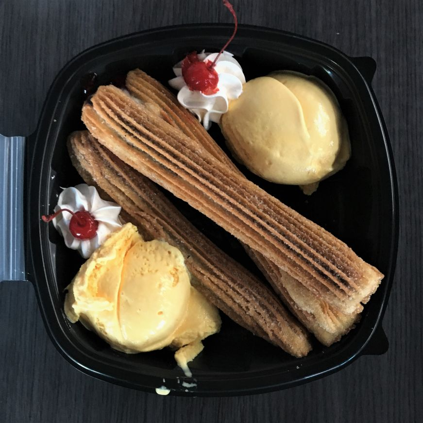 Three churros with two scoops of vanilla ice cream in take out box at Paleterias Tropicana, Kansas City