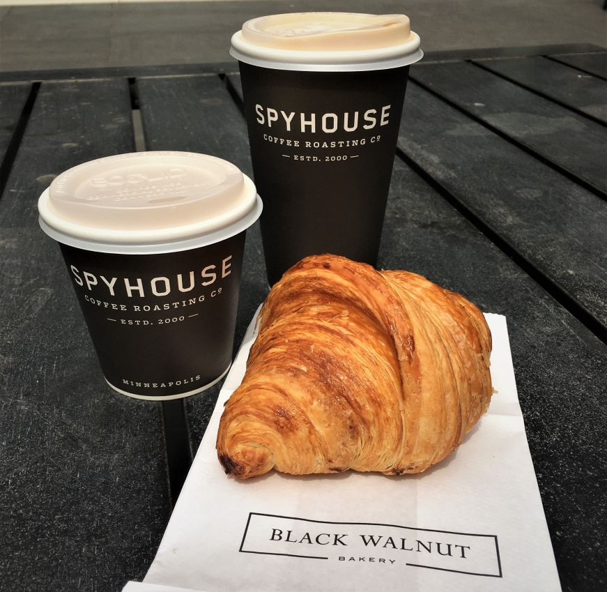 Two paper coffee cups with a croissant