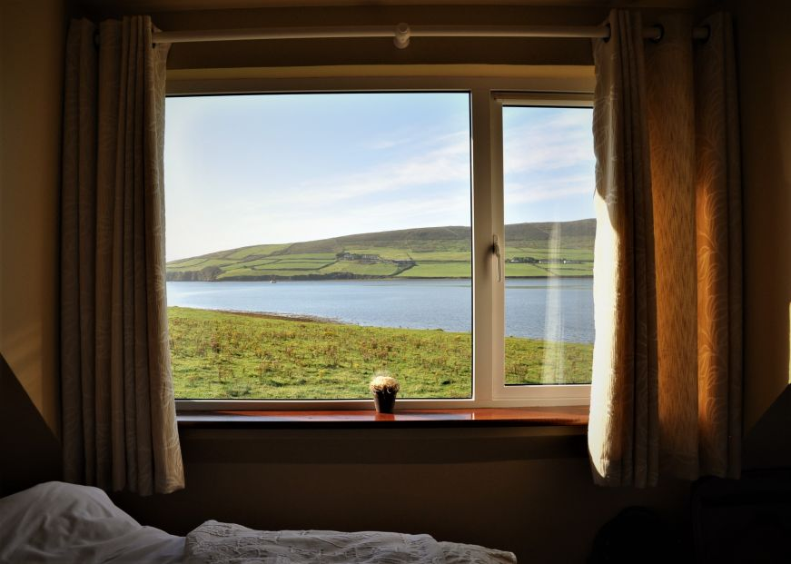 View of bay and rolling green hills through a bedroom window, Emlagh Lodge, Dingle, Ireland