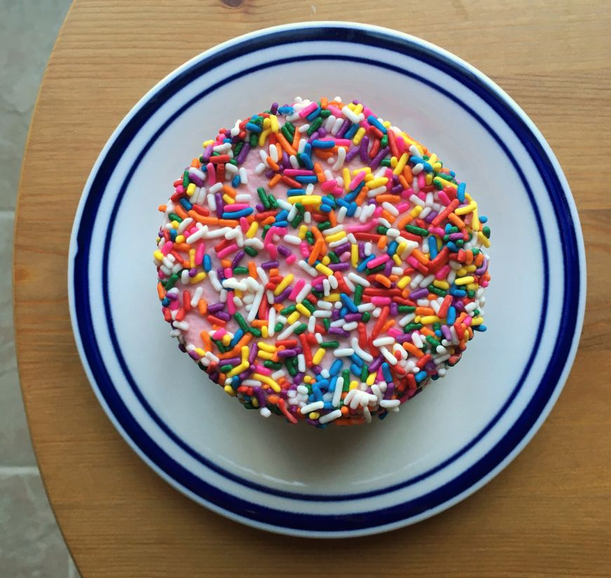 Individual sized cake covered with sprinkles