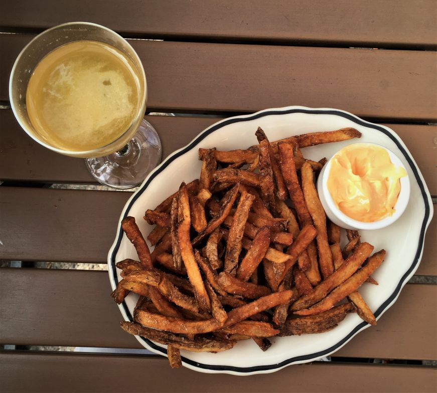Top down view of cocktail and plate of fries