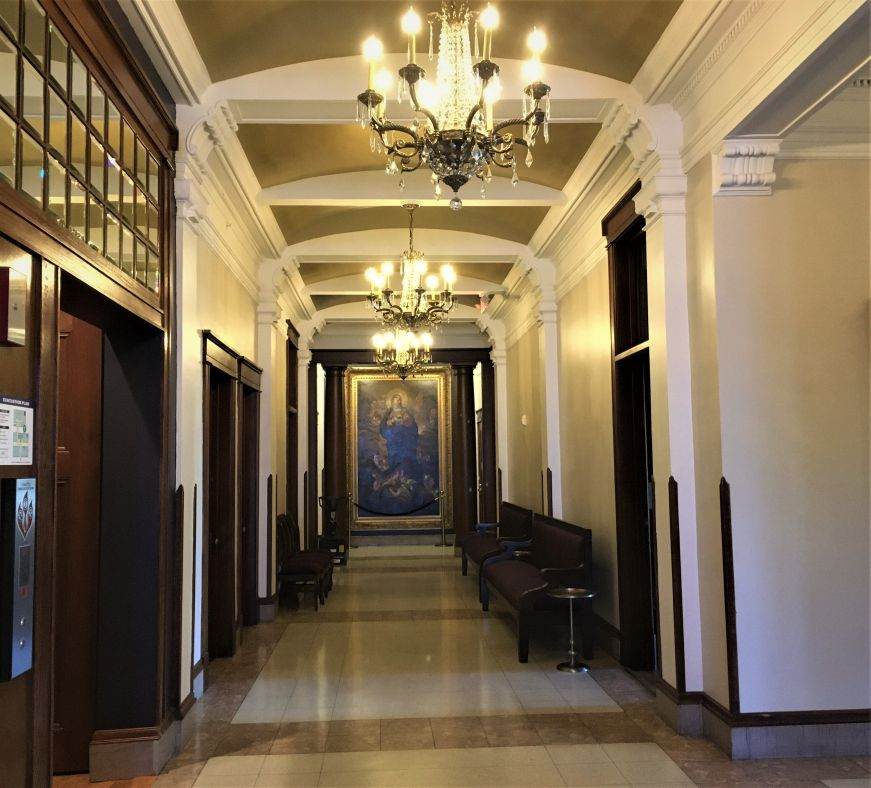 Hallway with ornate woodwork, religiously-themed oil paintings, and chandeliers