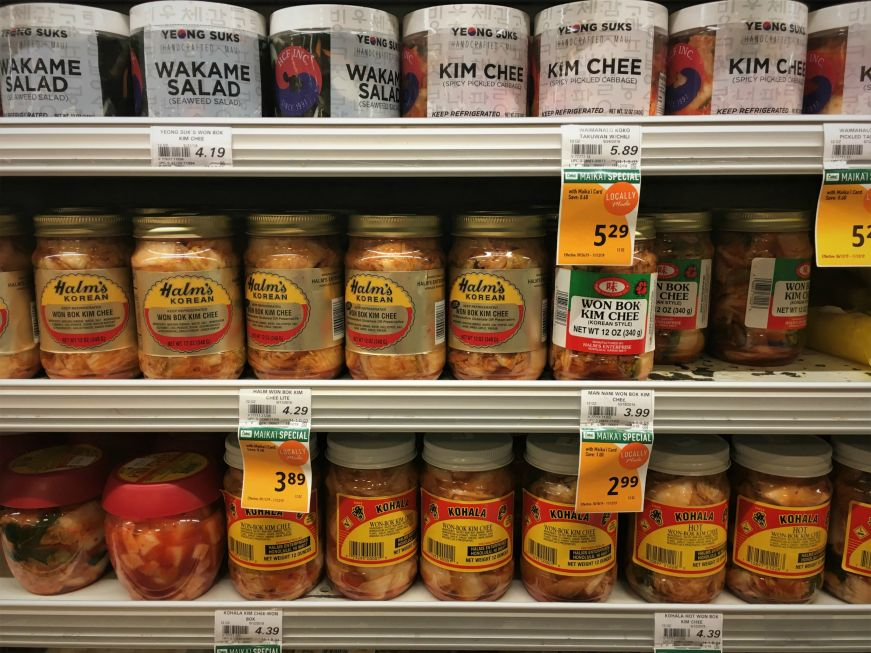 Jars of kimchi on shelves in the produce section of a grocery store, Hawaii