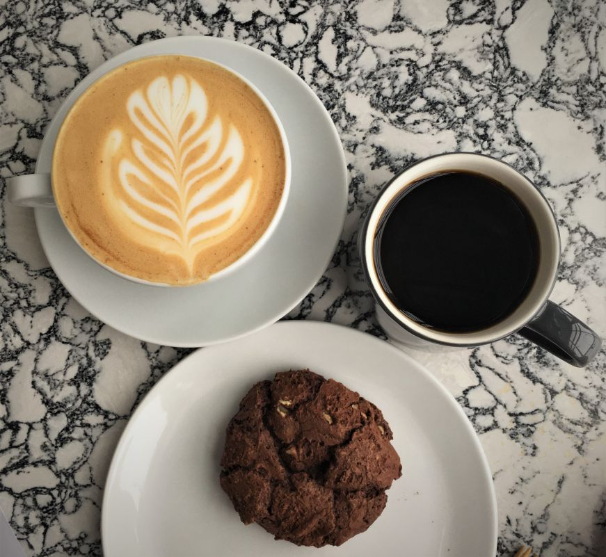Top down view of latte, cup of coffee, and chocolate cookie on a marble table, Parallel, Minneapolis