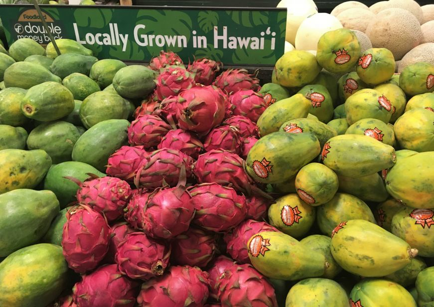 "Piles of papaya and dragonfruit with a sign reading ""Locally Grown in Hawai'i"" at a grocery store"