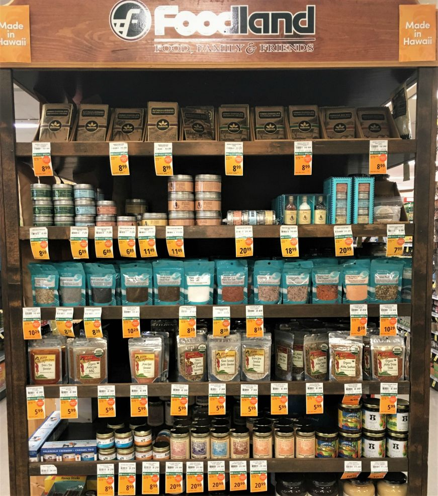 "Wooden shelves of seasonings with signs reading ""Made in Hawaii"" at a grocery store"