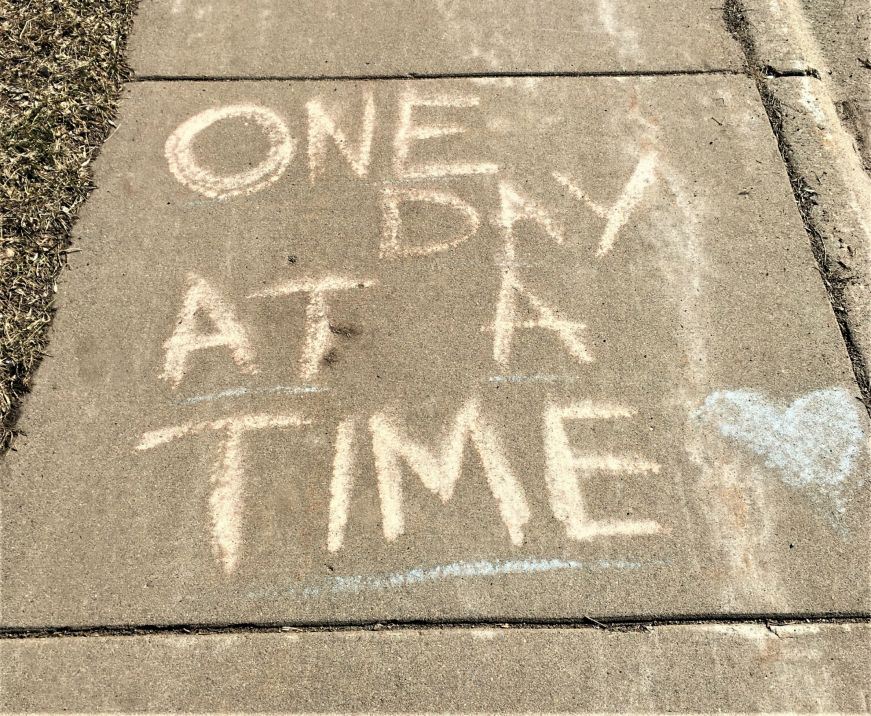 "Sidewalk with ""One day at a time"" written in chalk"