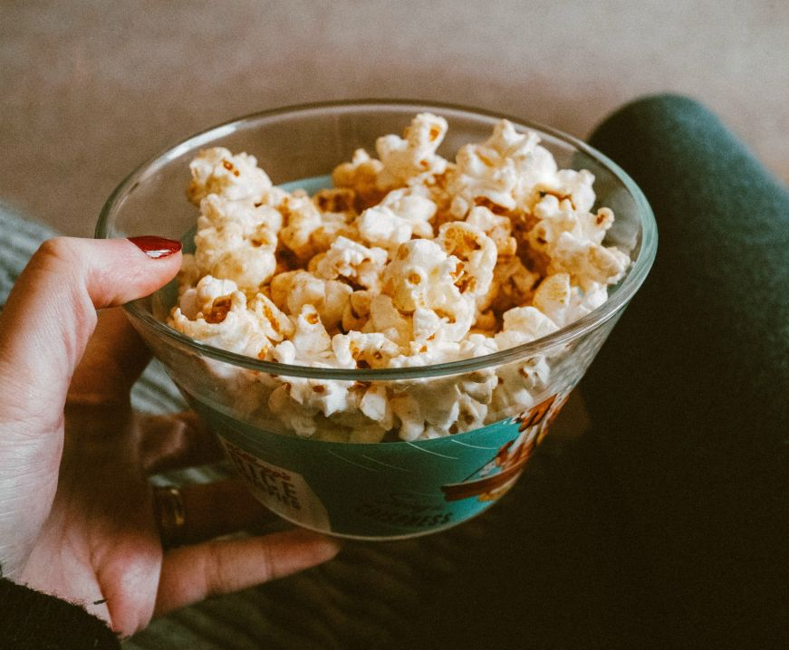 Hand holding glass bowl of popcorn