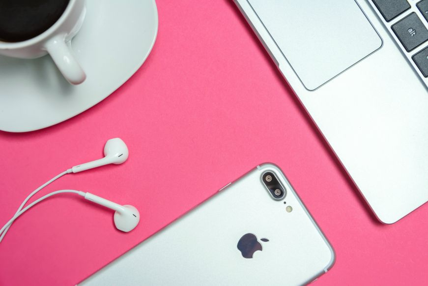 Top down view of iPhone, earphones, and laptop on a pink table