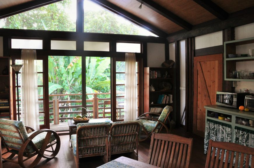 Cottage interior with a table, kitchenette, and couch with a view of lush tropical greenery through a glass door, Pua's Patch Airbnb, Papikou, Hawaii