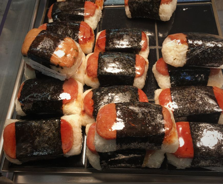 Spam musubi wrapped in plastic wrap underneath a heat lamp at a grocery store, Hawaii