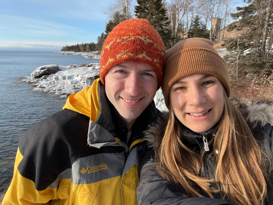 Stacy and Mike wearing winter clothes with Lake Superior in the background