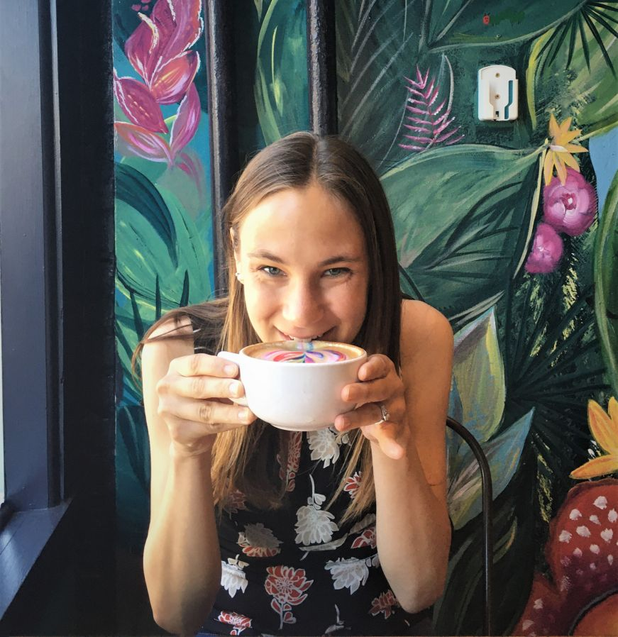 Stacy sipping a latte with a brightly colored jungle mural in the background