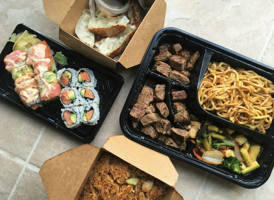Takeout containers with sushi rolls, dumplings, fried rice, and pieces of steak with vegetables and noodles