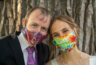 Stacy and Mike wearing wedding attire and face masks