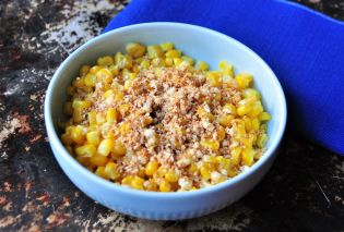 Bowl of corn topped with grated cheese and chipotle powder
