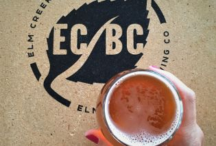 Top down view of hand holding beer over a table with the logo for Elm Creek Brewing Co.