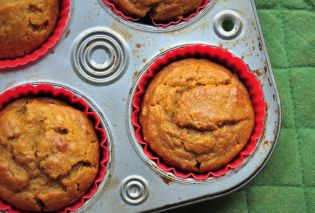Pumpkin muffins in a tin with a green potholder